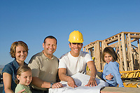 Portrait of family with two children (6-9) and construction side manager