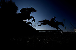 Runners in The 888Sport Pendil Novices' Steeple Chase clear an early fence at Kempton Park Racecourse.