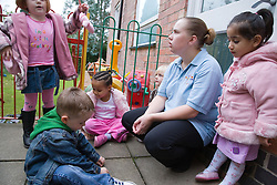 Group of playschool children with care assistant at breaktime,