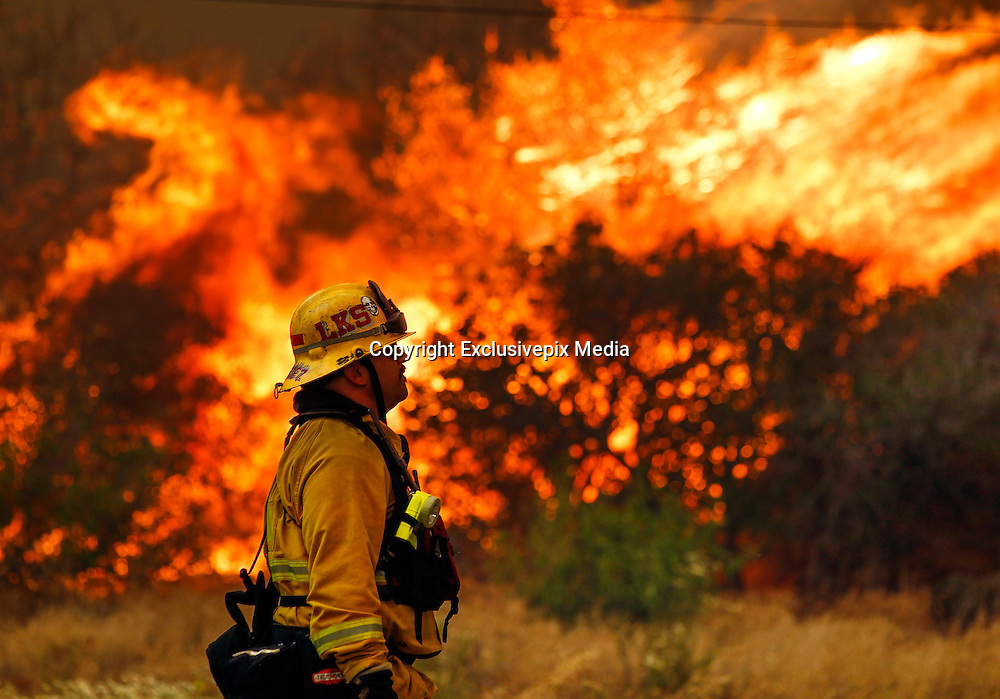 June 20, 2016 - Duarte, California, U.S. - Lakeside firefighter JOE VASQUEZ watches large flames burn next to a home on Highway 94 south of Potrero on Monday.<br /> &copy;Exclusivepix Media