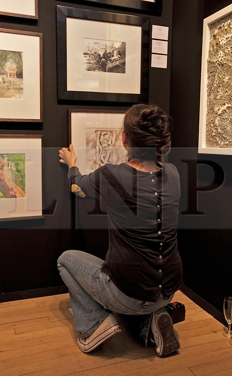 © Licensed to London News Pictures. 19/04/2012. London, U.K..Natasha Kumar from Artshouse puts up the pictures in their section. The Setting up of The Chelsea Art Fair in Chelsea Old Town Hall where Around 35 galleries and dealers offer modern British and contemporary art for sale, including paintings, drawings, etchings and sculptures. Represents 500 international artists, with art worth up to £20k. The fair runs from 19th April - 22nd April..Photo credit : Rich Bowen/LNP
