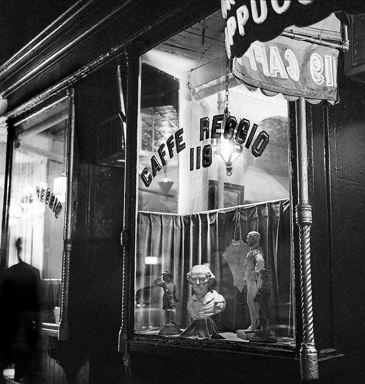 Caffe Reggio in 1957 during the heart of the coffee house culture. The window display reflects the aspirations of its patrons and others. The bust of Shakespeare looks directly at the camera, and the other figures and a plaque or shield are all carefully arranged. At the left is a person deliberately blurred as a reference to Giacometti, a major sculptor of the time. The young Bob Dylan and Joan Baez would have frequented this coffee house. Caffe Reggio is still going strong in 2017, but Shakespeare has exited and the window display is random.