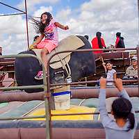 080214       Cable Hoover<br /> <br /> Ma'Tya Benally takes a turn on the mechanical bull during the Ramah Navajo Fair in Pine Hill Saturday.
