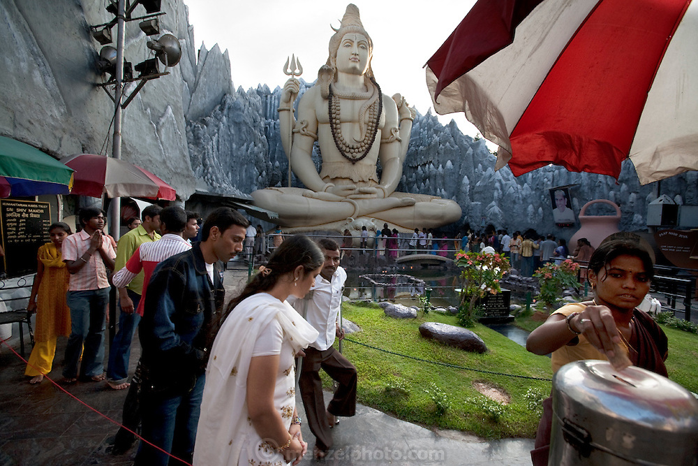Visitors wait for their turn to enter the Shiva Temple, which is built into the Kid's Kemp Shopping Mall on Old Airport Road in Bangalore, India. (From the book What I Eat: Around the World in 80 Diets.) The 65-foot plaster statue of Lord Shiva sits in a lotus position before an amusement park-style Himalayan mountain-scape built of chicken wire and cement. This free popular attraction at the Kids Kemp shopping mall draws nearly 500,000 devotees on festival days.