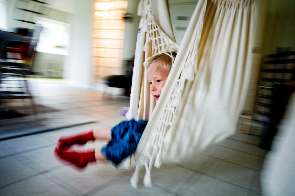 Julius, 4, the son of Måns Persson and Pernilla Cederlund, playing in a swing inside their summer house in Vitaby, Skåne