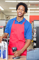 Portrait of an African American male store clerk standing at checkout counter