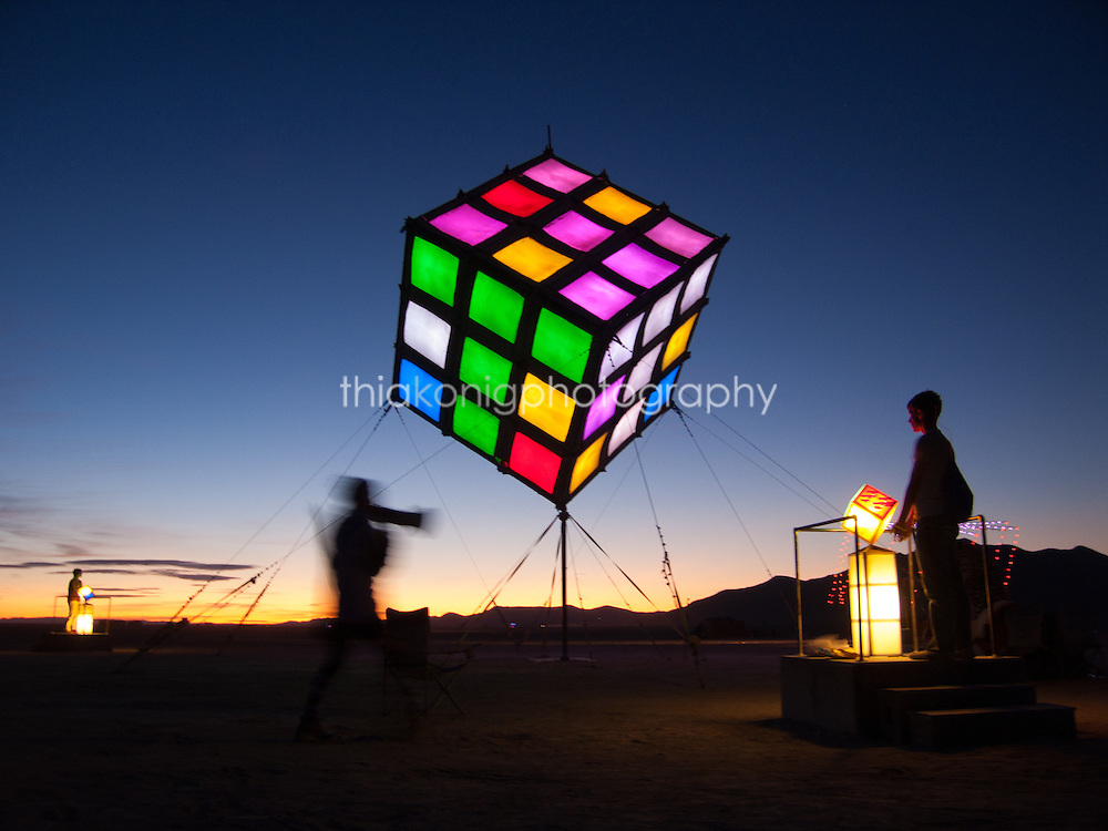 The artist instructs a volunteer to play and help solve a giant Rubiks cube puzzle before dawn at Burning Man.