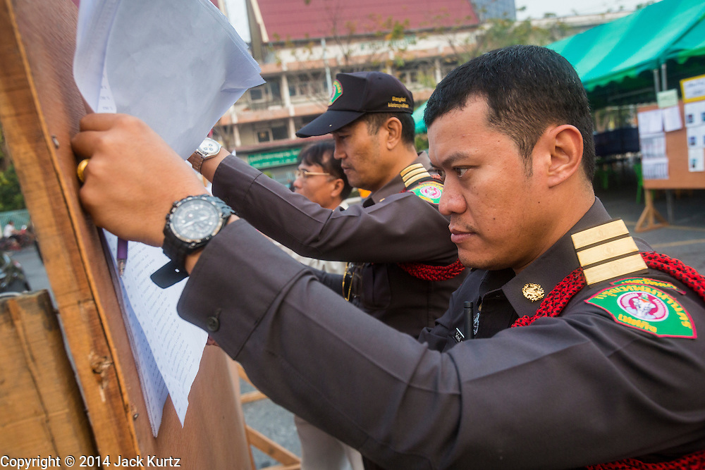 26 JANUARY 2014 - BANGKOK, THAILAND:  Thai police officers look up their names of a list of registered voters at the Wat That Thong polling place in Bangkok. The officers did not get to vote because the polling place was shut down by anti-government protestors. Early voting was supposed to be Sunday January 26 but blocked polling places left hundreds of thousands of people unable to vote casting the February 2 general election into doubt and further gridlocking Thai politics. Anti-government protestors forced the closure of polling places in Bangkok Sunday as a part of Shutdown Bangkok. Protestors blocked access to gates and entry ways to polling places and election officials chose the close them rather than confront protestors. Shutdown Bangkok has been going for 12 days with no resolution in sight. Suthep, the leader of the anti-government protests and the People's Democratic Reform Committee (PDRC), the umbrella organization of the protests,  is still demanding the caretaker government of Prime Minister Yingluck Shinawatra resign, the PM says she won't resign and intends to go ahead with the election.   PHOTO BY JACK KURTZ