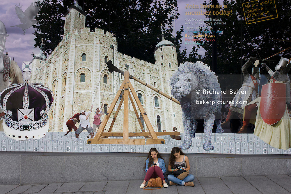 Young tourist women sit beneath the large UK tourism window featuring famous landmarks, at the Tower of London.