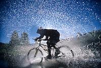 Mountain Bicyclist Splashing Through Water side view