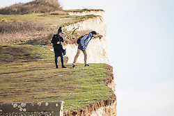© Licensed to London News Pictures. 04/02/2018. Brighton, UK. Members of the public stand close to the edge of the Birling Gap and Beachy Head cliffs.  Photo credit: Hugo Michiels/LNP