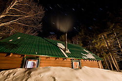 Stars above a cozy cabin in winter at Medawisla Wilderness Camps near Greenville, Maine.