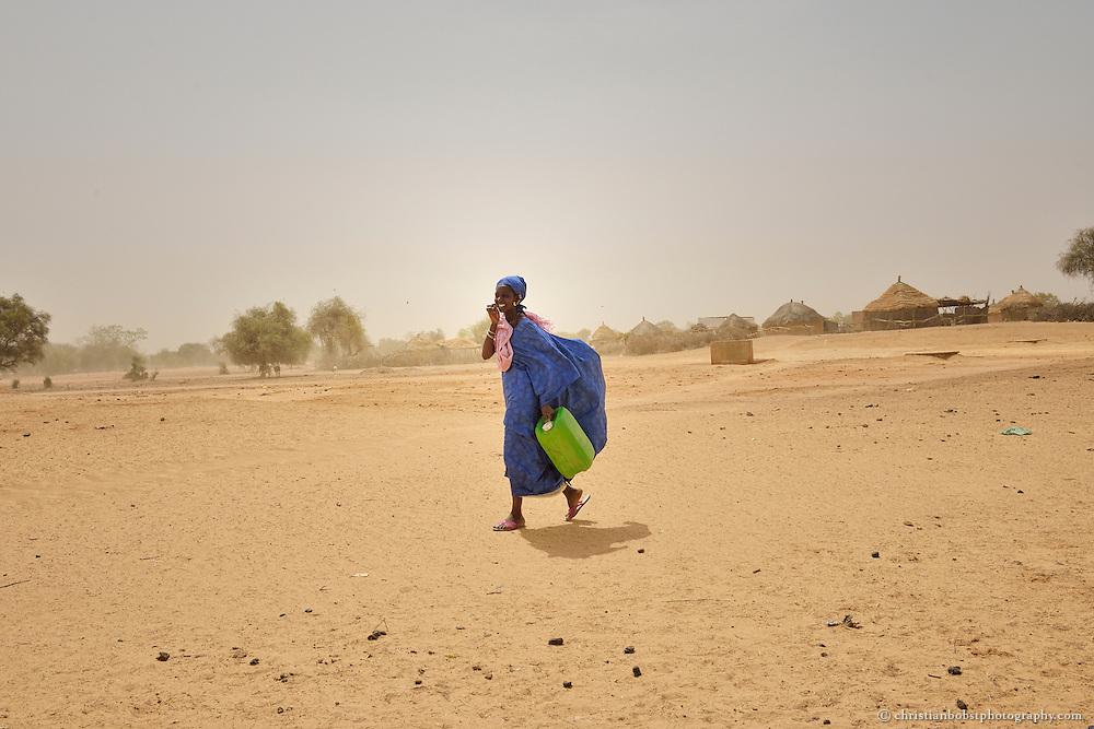 Dank eines von HEKS mitfinanzierten Bohrbrunnen können Frauen im sehr heissen und trockenen YOUNOUFERE in Senegal einen Garten anlegen und  Gemüse anbauen. Eine Frau auf dem Weg von ihrer Hütte zum Brunnen des Gartens.