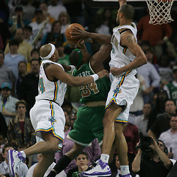 Paul Pierce #34 shoots as Hornets Tyson Chandler (right) and Bonzi Wells (left) defend in the third quarter of their NBA game on March 22, 2008 at the New Orleans Arena in New Orleans, Louisiana.