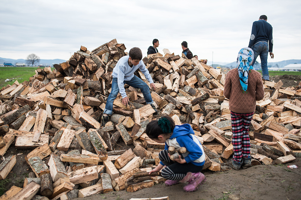 Children are collecting logs for lighting fires to cook, warm and dry their clothes in a field in Idomeni, Greece. <br /> <br /> Thousands of refugees are stranded in Idomeni unable to cross the border. The facilities here are stretched to the limit and the conditions are appalling. It's raining, it's cold there is mud everywhere and there is no hope that the border will open anytime soon.