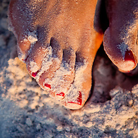 Toes and red lipstick are caked with soft sand behind Loews Don CeSar Beach Resort on St. Pete Beach.