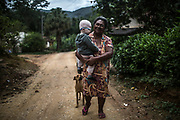 Neire de Souza  walks her grandson Felipe through the unpaved streets of Ivaporunduva quilombo (former runaway slave communal land) in Eldorado, south of Sao Paulo, Brazil, Monday, Nov. 26, 2018. (Dado Galdieri)