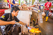"03 OCTOBER 2012 - BANGKOK, THAILAND:     A worker burns hair off pig's feet in Khlong Toey Market in Bangkok. Khlong Toey (also called Khlong Toei) Market is one of the largest ""wet markets"" in Thailand. Thousands of people shop in the sprawling market for fresh fruits and vegetables as well meat, fish and poultry every day.       PHOTO BY JACK KURTZ"