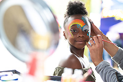 © Licensed to London News Pictures . 12/08/2018. Manchester , UK . KIERA PAYNE (eight) from Rusholme has her face painted . The second day of the annual Caribbean Carnival in Alexandra Park in Moss Side , celebrating music , food and Afro-Caribbean culture . A nearby shooting overnight lead to at least ten people injured . Ten people are in hospital . Photo credit : Joel Goodman/LNP