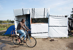 "© Licensed to London News Pictures. 30/08/2015. Calais, France. A refugee rides a bike in the camp, also known as the Jungle, at Calais. Today around a hundred British cyclists from ""Bikes Beyond Borders"" arrived at the refugee camp in a two-day ride from London to donate bicycles and supplies to support the life at the site. Photo credit : Isabel Infantes/LNP"