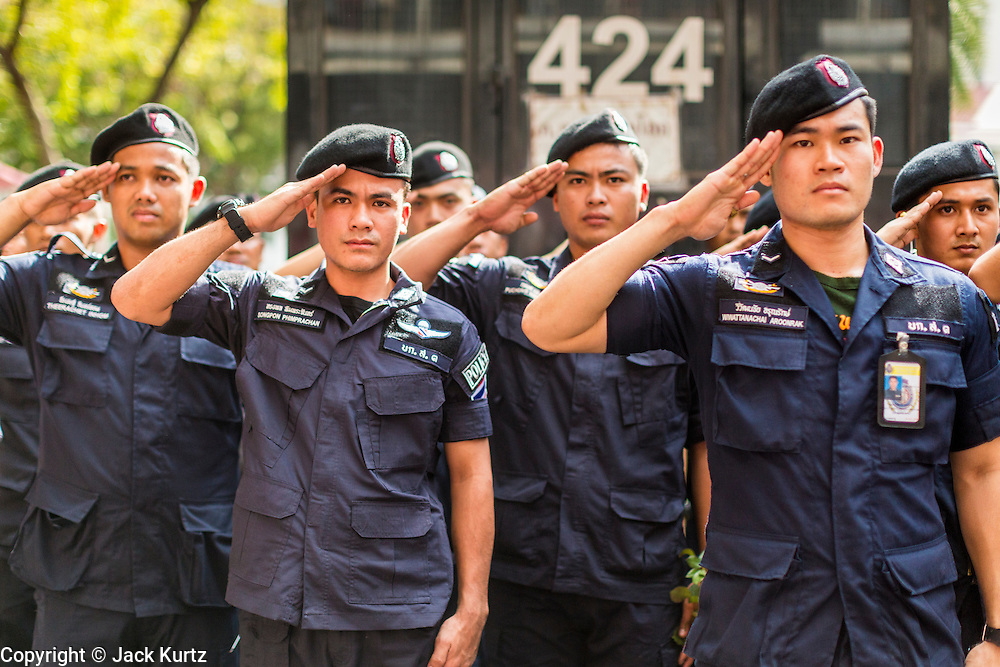 27 NOVEMBER 2013 - BANGKOK, THAILAND: Thai riot police salute while protestors sing the King's Anthem at police headquarters in Bangkok. About 500 people from the Silom area of Bangkok walked to Royal Thai Police Headquarters on Rama I Road and presented police officers with roses and orchids. The action was one of the continuing anti-government protests gridlocking the Thai capital. After the meeting at police headquarters the protestors joined other protestors at the Ministry of Finance. Protests also spread to other government ministries and several provinces in southern Thailand, a stronghold of the opposition.      PHOTO BY JACK KURTZ