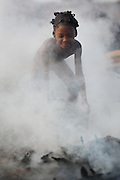 A girl stands in thick smoke as she splashes water on hot charcoal at a wood charcoal production site on the outskirts of San Pedro, Bas-Sassandra region, Côte d'Ivoire on Sunday March 4, 2012. Men, women and children - who don't go to school - work here seven days a week.
