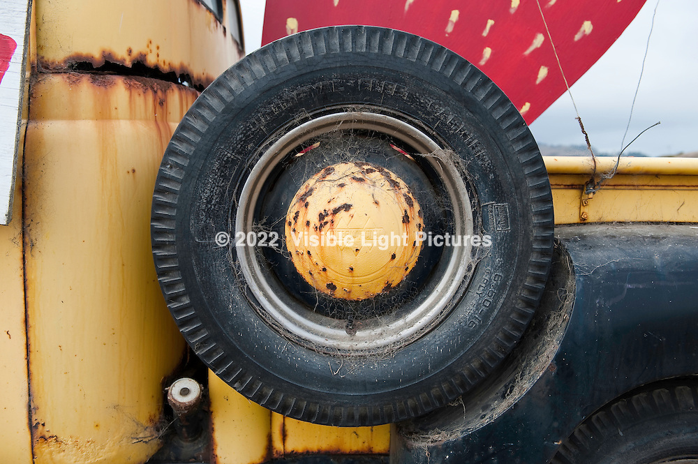Spare tire on the side of an old, rusted black and yellow pick-up truck.