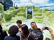 22 OCTOBER 2017 - BANGKOK, THAILAND: People photograph floral displays in front of Pak Khlong Talat, the flower market, in Bangkok. There is a replica crematorium south of the flower market and the street in front features elaborate displays in the late king's honor. The King died in October 2016 and will be cremated on 26 October 2017.     PHOTO BY JACK KURTZ