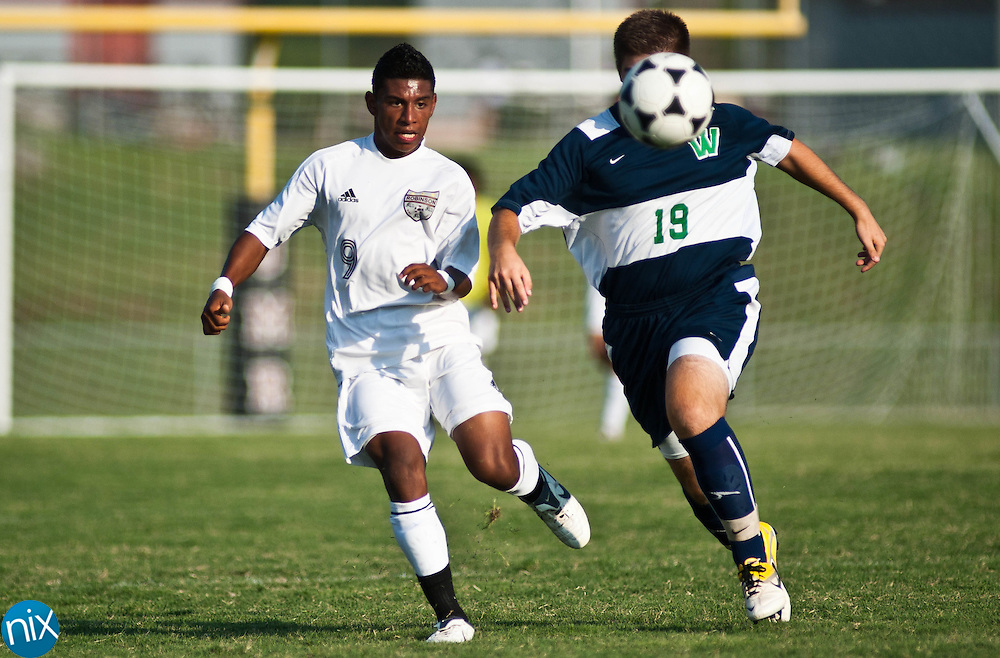 Jay M. Robinson's Uriel Rebollar kicks the ball ahead of Weddington's Harris Pistiolis Wednesday night in Concord. (photo by James NIx)