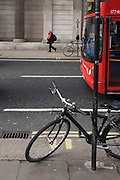 Londoner, red bus and two bicycles locked to posts on opposite sides of the road outside the Bank of England in the City of London.