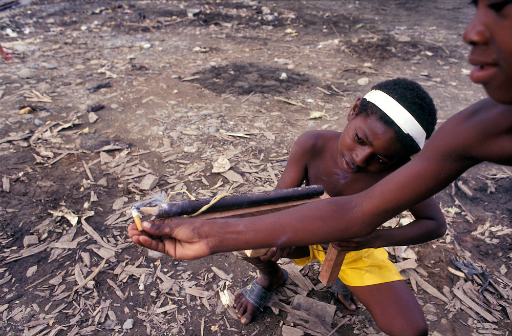 Children of Quibdo, El Choco, ignite a toy gun which fires real projectiles, using a cigarette. Colombia