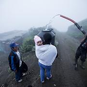 """Anna-Rosa e sua figlia Vercy aspettano che l'addetto del camion riempa il loro """"tank"""". Un tank può contenere fino a 120 litri."""