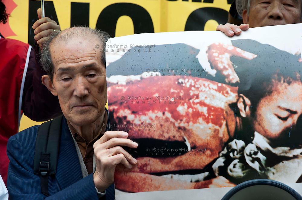 """Roma 16 Marzo 2011.Piazza della Rotonda al Pantheon.Manifestazione dei Verdi per denunciare la pericolosità delle scelte del Governo di un ritorno al nucleare in Italia.Partecipano all'iniziativa due cittadini giapponesi,Tsuboi Susumu di Hiroshima, 83 anni,  e Hiroshi Suenaga di Nagasaki, 75 anni. sopravvissuti alle bombe atomiche sganciate su Hiroshima e Nagasaki dagli americani alla fine della Seconda Guerra Mondiale. I due giapponesi stanno facendo il giro del mondo con la nave """"Peace Now""""  per dire no al nucleare. I due sopravvissiti mostrano gli effetti della bomba atomica su un ragazzo..Rome March 16, 2011.Al Pantheon Piazza della Rotonda.Demonstration of the Greens pointed out the dangerousness of the government's choice of a return to nuclear power in Italy. Participating two Japanese citizens of Hiroshima Susumu Tsuboi, 83 years, Hiroshi Suenaga and Nagasaki 75 years. survived the atomic bombs dropped on Hiroshima and Nagasaki by the Americans at the end of Second World War. The two Japanese are doing around the world with the ship """"Peace Now""""to say no to nuclear."""