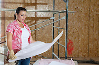 Young female contractor looking at building plans with scaffold in background