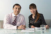 Business man and woman at table in office portrait