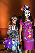 Young Mexican girls wearing skeleton face paint during the Dead of the Dead festival in San Miguel de Allende, Mexico. The multi-day festival is to remember friends and family members who have died using calaveras, aztec marigolds, alfeniques, papel picado and the favorite foods and beverages of the departed.