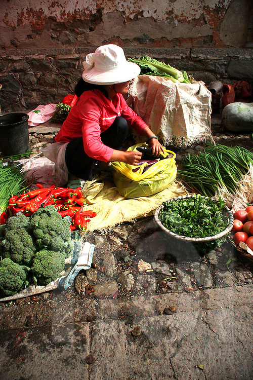 A woman is selling vegetables on the market place of the village. She's smiling to an other seller, packaging aubergine.