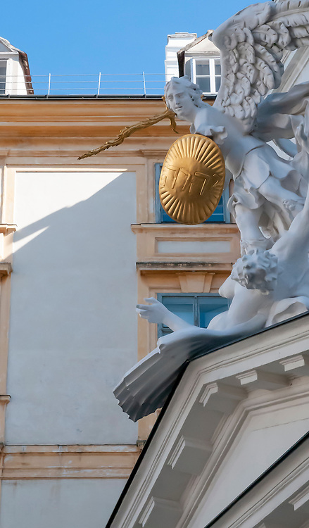 A smiting angel statue wielding a sword and holding a Jehovah shield at the Hofburg Palace, Vienna, Austria.