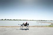 Een roeifietsers rijdt mee met de stroopwafeltocht.<br /> <br /> A man on a rowing bike is passing a river