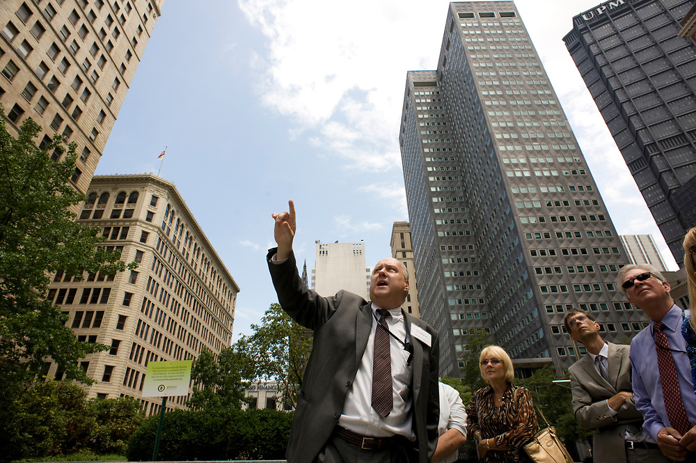 Docent Sam Webb (left) of the Pittsburgh Parks Conservancy, leads a tour of Mellon Square for Federated Investors employees at lunchtime in downtown Pittsburgh. Renovations for the landmark park are scheduled to begin this year.