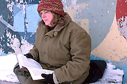 Homeless woman age 41 reading bible in the dead of winter.  St Paul Minnesota USA