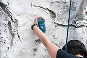 Young teen girl climbs up an artificial climbing wall Model release available