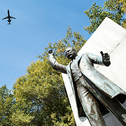 Statue of America's 26th president at the Theodore Roosevelt Memorial. At top left, a plane comes in to land at the nearby Reagan National Airport.