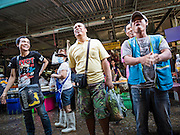 "12 JUNE 2015 - BANGKOK, THAILAND: Thais watch the Thai women's football (soccer) team play in the Women's World Cup on television on a TV hanging in Khlong Toey Market. Khlong Toey (also called Khlong Toei) Market is one of the largest ""wet markets"" in Thailand. The market is located in the midst of one of Bangkok's largest slum areas and close to the city's original deep water port. Thousands of people live in the neighboring slum area. Thousands more shop in the sprawling market for fresh fruits and vegetables as well meat, fish and poultry.          PHOTO BY JACK KURTZ"