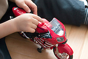Child age 3 pushing button on new wheelie motorcycle. Pushing your buttons concept. Balucki District Lodz Central Poland