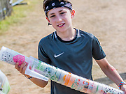 Henham Park, Suffolk, 20 July 2019. An enterprising boy makes money by collecting cups discarded by people despite them having paid a deposit on them. The 2019 Latitude Festival.