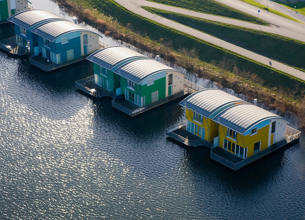 Nederland, Gelderland, Maasbommel, 11-02-2008; floating houses in the river Maas, rise and fall with the water - the homes are part of a holiday complex and are build outside the dike (on the river side in the floodplain; drijvende woningen aan de Bovendijk, bij het recreatiegebied De Gouden Ham, onderdeel van de rivier de Maas; de recreatiewoningen maken onderdeel uit van een complex van buitendijks gebouwde tweede huizen, die (gaan) drijven bij hoog water; de woningen zijn bevestigd aan meerpalen om de verschillen in waterhoogte op te vangen;.ruimte voor de rivier, wateroverlast, hoog water, waterhuishouding, waterbeheer, watermanagement, wonen, water, klimaatverandering, global warming, milieu, waterwoningen, innovatie;.room for the river, flooding, high water, water resources, water management, water management, climate change, global warming, environment, living, water, housing, innovation, climate change, carbon dioxide, greenhouse gases, warming of the planet.luchtfoto (toeslag); aerial photo (additional fee required); .foto Siebe Swart / photo Siebe Swart