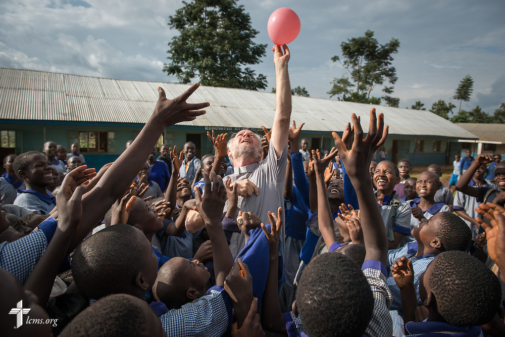 The Rev. Dr. John Juedes, pastor of Messiah Lutheran Church in Highland, Calif., plays with school children Friday, June 13, 2014, at the Luanda Doho Primary School in Kakmega County, Kenya. LCMS Communications/Erik M. Lunsford