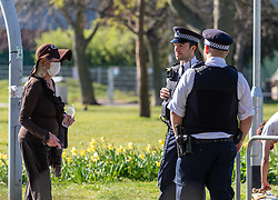 © Licensed to London News Pictures. 05/04/2020. London, UK. Police question a women in a mask in Normand Park, Fulham as members of the public come out to exercise as temperatures reach over 21c this weekend. The Government has urged the public not to leave home during the fine weather to help save lives as the Coronavirus crisis continues. Photo credit: Alex Lentati/LNP