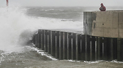 © Licensed to London News Pictures. 03/03/2019. West Bay, UK. A man looks at the sea at West Bay in Dorset as storm Freya whips up the waves. Photo credit: Jason Bryant/LNP